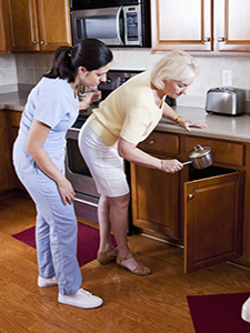 Home Care giver helping senior lady in kitchen